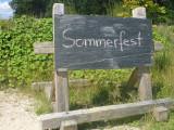 """Rechteckge Steintafel mit der Aufschrift """"Sommerfest"""" Im Hintergrund Bäume und Sträucher"""