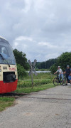 Die Biberbahn fährt auf den Schienen an einem Bahnübergang ohne Schranken warten sechs Fahrradfahrer
